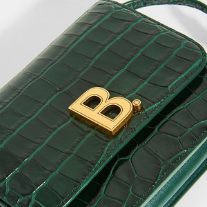 Close up detail of gold B hardware on BALENCIAGA B Small Bag in Croc-Embossed Calfskin