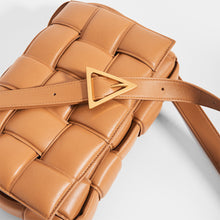 Load image into Gallery viewer, Top view of BOTTEGA VENETA Padded Cassette Crossbody Bag in Caramel Lambskin Leather