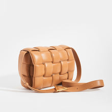 Load image into Gallery viewer, Side view of BOTTEGA VENETA Padded Cassette Crossbody Bag in Caramel Lambskin Leather