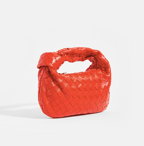 Side view of the BOTTEGA VENETA Mini Jodie Intrecciato Leather Top Handle Bag in Red