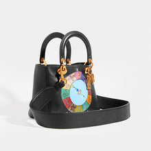 Load image into Gallery viewer, Side view of DIOR Vintage Lady Dior Wheel of Fortune Bag in Black leather with hand-painted detail and black leather strap