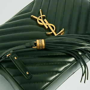 Close up detail of gold YSL hardware and leather tassel on the SAINT LAURENT Lou Camera Bag in Dark Green Matelassé Leather