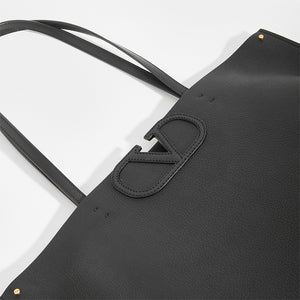 Detail of V logo on VALENTINO Garavani Fill Me Tote in Black Leather