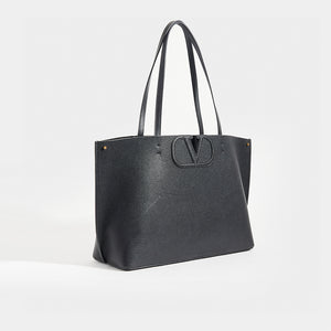Side view of VALENTINO Garavani Fill Me Tote in Black Leather