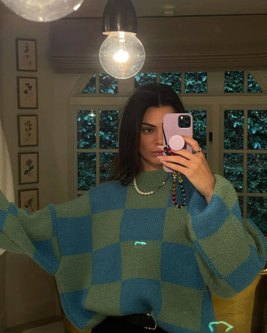 Kendall Jenner wears a checked jumper and a pearl and bead necklace