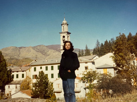 A woman in the 1980s in front of an Italian mountain village
