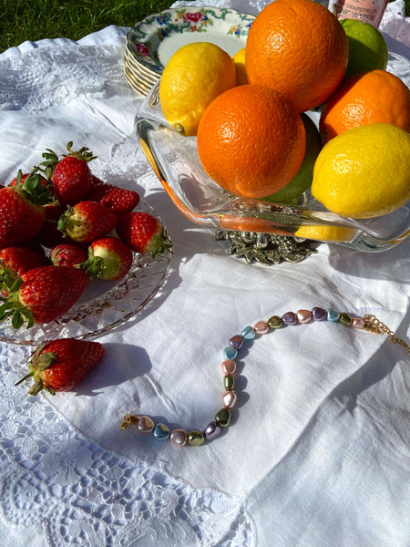 An anklet made of pastel coloured crystal pearls surrounded by fruit.