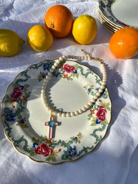 A round pearl necklace in white with a pink cross pendant on a white picnic cloth surrounded by oranges and lemons