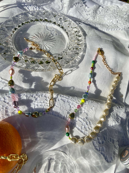 Two necklaces made from pearls, beads and gold chain on a white picnic cloth