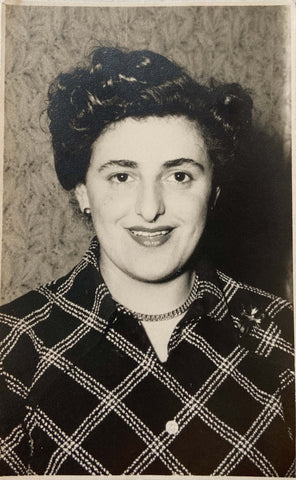 A black and white photo of a woman wearing a checked shirt and necklace in the 1950s