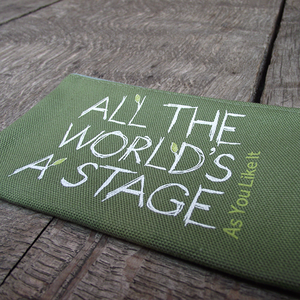 Sage green cotton zipped purse with a quote from Shakespeare play, As You Like It (all the world's a stage) printed in white. The lettering is hand-drawn in a scribbled style and several of the letters have little lime green leaves 'growing' from them. The title of the play is printed in lime green up the right hand side of the quote.