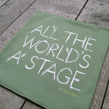 Sage green cotton cushion cover printed with a quote from Shakespeare play, As You Like It (all the world's a stage). The lettering is printed in white in a scribbled style to represent wood and there are several lime green leaves growing from the letters. The title of the play is printed in lime green under the quote.