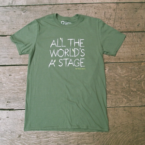 Sage green t-shirt with a round neckline. The t-shirt has a quote from Shakespeare play, As You Like It (all the world's a stage) printed in white centrally on the chest. The lettering is hand-drawn in a scribbled style to represent woodgrain and several of the lettering have lime green leaves growing out of them. The title of the play is printed in lime green under the quote.