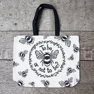 Tote bag made of heavyweight unbleached cotton canvas with mid-length black webbing handles. The bag is printed with a black design adapted from an original print of a bumble bee with a striped body and paneled wings, and a quote from Shakespeare play, Hamlet (To be or not to be?). In a ring around the bee and the quote are flowers and leaves. Outside this main design are a number of smaller bees flying in different directions.