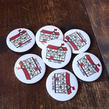 Button badge featuring a friendly drawing of Shakespeare's Globe Theatre.