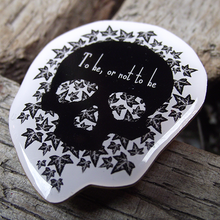 Pin badge with a black skull and a quote from Hamlet (to be, or not to be)