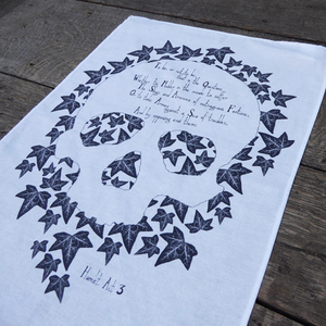 White cotton tea towel printed in grey with ivy leaves. The void in the leaves forms the shape of a skull. Across the forehead of the skull are the first lines from Hamlet's to be or not to be soliloquy from Shakespeare play, Hamlet.