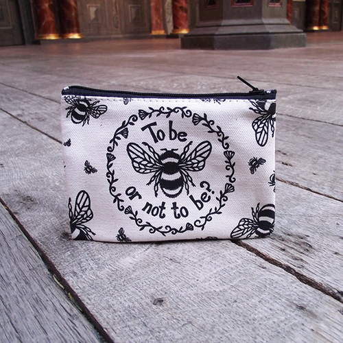 Rectangular purse made from unbleached cotton with a black zip closure. The purse is printed with a design adapted from an original print in black, a bumble bee and a quote from Shakespeare play, Hamlet (to be or not to be) is surrounded by a ring of flowers and leaves. Smaller bees surround the central image, flying in different directions.