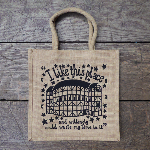 Unbleached jute bag with unbleached cotton handles printed with a design based on an original print in black. The design features a simplified image of the Globe Theatre with the frame on view. the theatre is surrounded by stars and a quote from Shakespeare play, As You Like It is above and below the theatre (I like this place and willingly could waste my time in it).