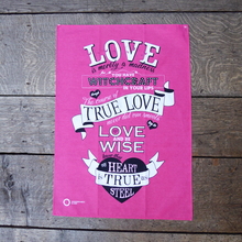 Pink cotton tea towel with a selection of quotes about love from Shakespeare plays. The quotes are printed in black and white and are hand-drawn.