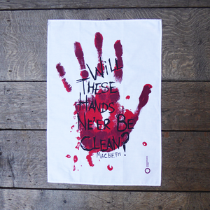 White cotton tea towel printed with a large bloody hand-print in reds. Over the hand-print, printed in black is a quote from Shakespeare play, Macbeth (Will these hands ne'er be clean?) The lettering is in an angry, hand-drawn style.