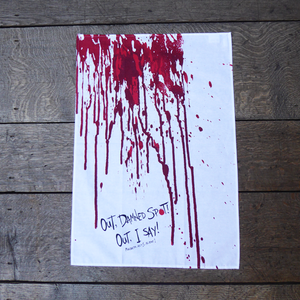 White cotton tea towel with a print of blood dripping down the length of the towel, in reds. At the bottom of the towel is a quote from Shakespeare play, Macbeth (Out. damned spot! Out, I say!) The quote is written in an angry hand-drawn style in black.