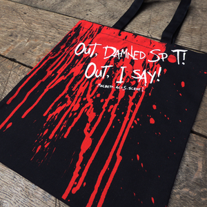 Black cotton bag with mid-length black handles. The bag is printed with a realistic blood spatter in red which drips down from the top to the bottom. Across the blood, printed in white hand-drawn capital letters is a quote from Shakespeare play, Macbeth (Out, damned spot! Out, I say!) The title of the play is printed in white beneath the quote.