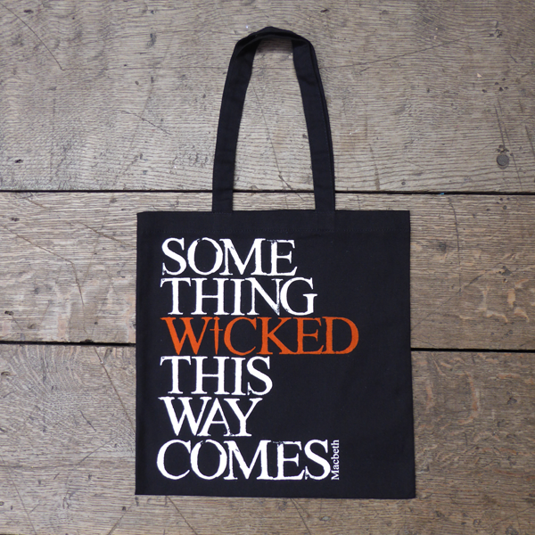 Black cotton bag with mid-length black handles printed with a quote from Shakespeare play, Macbeth (Something wicked this way comes). The lettering is bold serifed capital letters which are slightly distressed printed in white, except for 'WICKED) which is printed in orange. The 'I' of wicked is replaced by a dagger.