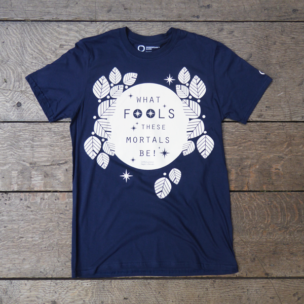 Navy blue cotton t-shirt with a round neck, printed with a motif in white. The motif consists of a white circle (to represent the full moon) surrounded by stylised leaves and stars, also in white. Across the face of the moon is a quote from Shakespeare play, A Midsummer Night's Dream (what fools these mortals be!) in navy blue. The lettering is in a slim modern san serif font in capitals.