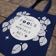 A  cotton book bag for Shakespeare's Globe. The bag is midnight blue with mid-length matching handles. Printed on the bag in white is a design consisting of a white circle (to represent the full moon) surrounded by stylised white leaves and stars. Across the face of the moon is a quote from Shakespeare play, A Midsummer Night's Dream (What fools these mortals be!) in midnight blue. The lettering is slim capitals.