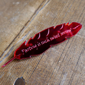 Red mirrored acrylic brooch shaped like a quill and engraved with a quote from Romeo and Juliet