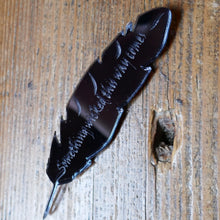 Black, mirrored acrylic brooch in the shape of a quill, with a quote from Shakespeare's Macbeth