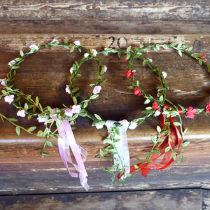 Wire and paper flower crowns. Wire wrapped in green paper leaves and a choice of red, pink or white paper flowers. Finished with matching ribbons.