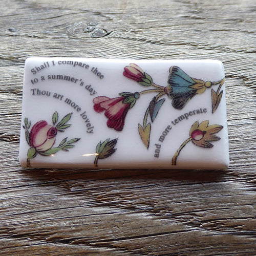 Rectangular ceramic brooch with lines from Shakespeare's Sonnet 18 and images of flowers