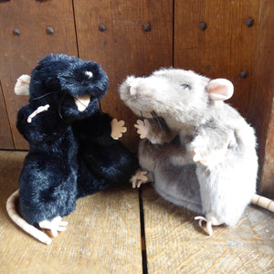 Plush rat hand puppet (black or grey) with light pink felt paws, ears and nose and a pink felt tail. Photographed in the Globe Theatre.