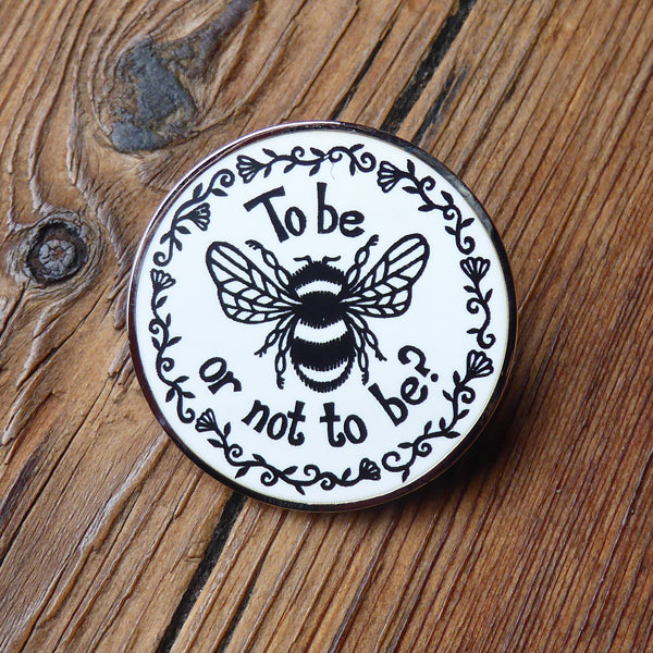 Metal pin badge with a bumble bee design and a quote from Shakespeare's Hamlet