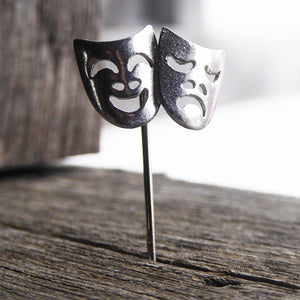 Pewter comedy (laughing face) and tragedy (crying face) are joined together and attached to a steel pin.