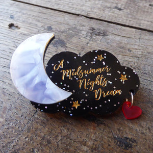 Acrylic brooch with a moon and a cloud of stars design, engraved with A Midsummer Night's Dream in gold