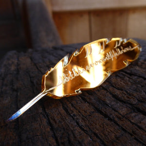 Gold mirrored acrylic brooch in the shape of a quill, engraved with a quote from Hamlet