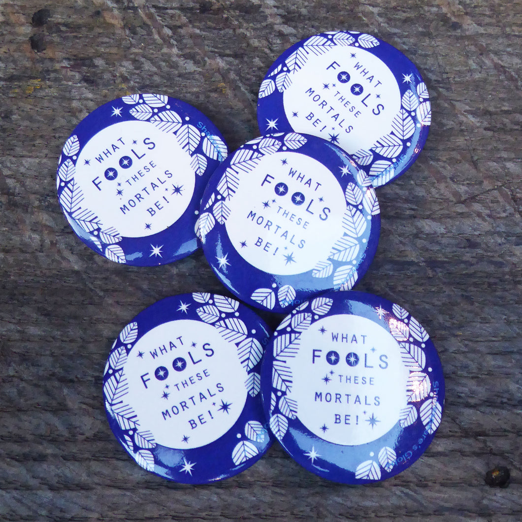 Button badge with a blue and white design. The design shows a white full moon surrounded by stylised white leaves and stars. Across the face of the moon is a quote from Shakespeare play, A Midsummer Night's Drea, (What fools these mortals be!) printed in blue.