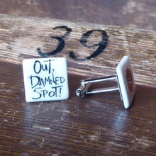 Ceramic cufflinks featuring a quote from Lady Macbeth on one (Out, damned spot!) and a blood spot on the other