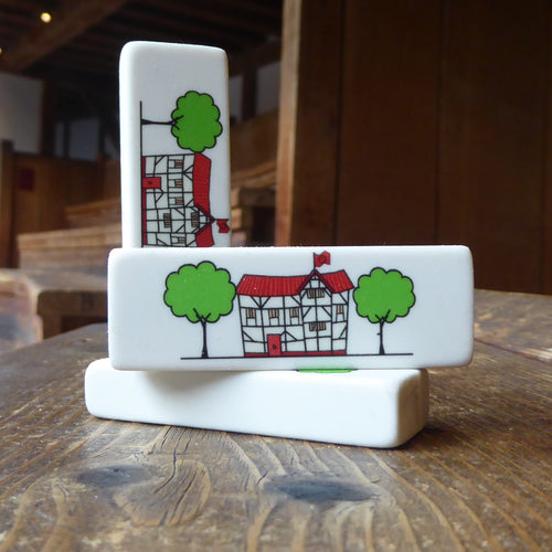Rectangular white eraser with a print of an illustration of the Globe Theatre in black outline. The theatre also has a red roof and door and is flanked by two green trees.
