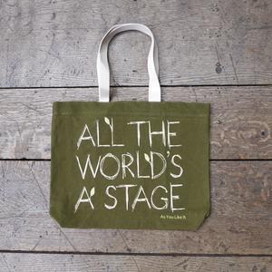 Sturdy sage green tote bag with a quote from Shakespeare play As You Like It (all the world's a stage) printed in white. The lettering is in a hand-drawn scribbled style to represent woodgrain and several of the letters have little lime green leaves growing out from them. The title of the play is printed in lime green under the quote. The bag has white handles.