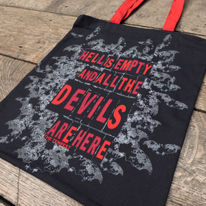 Black cotton bag with red mid-length handles. The bag is printed with a quote from Shakespeare play, The Tempest (Hell is empty and all the devils are here) in bold, san serif, capital letters. Surrounding the quote is a cloud of grey bats flying out as if from hell.