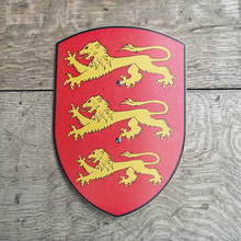 Wooden toy shield with three yellow lions on a red background. Photographed on the Globe Theatre stage.