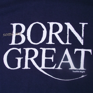 "Close up of navy blue t-shirt with a quote from Shakespeare play, Twelfth Night. Quote reads ""Some are born great"""