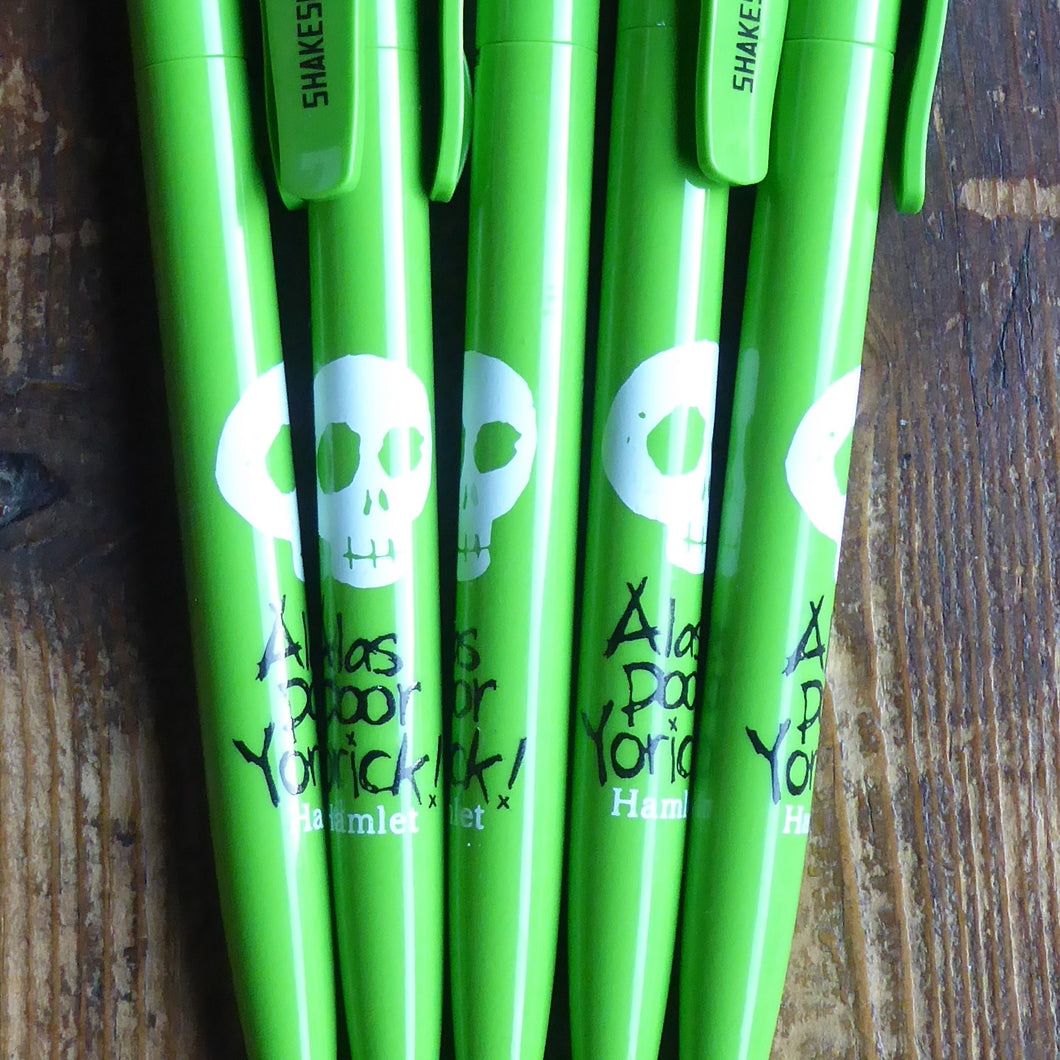 Bright green ballpoint pen with a printed quote on the barrel. The quote from Shakespeare play, Hamlet, is printed in black handdrawn letters (Alas poor Yorick!) Above the quote is a skull printed in white. The name of the play is printed in white under the quote. The Shakespeare's Globe logo is printed in black on the clip.