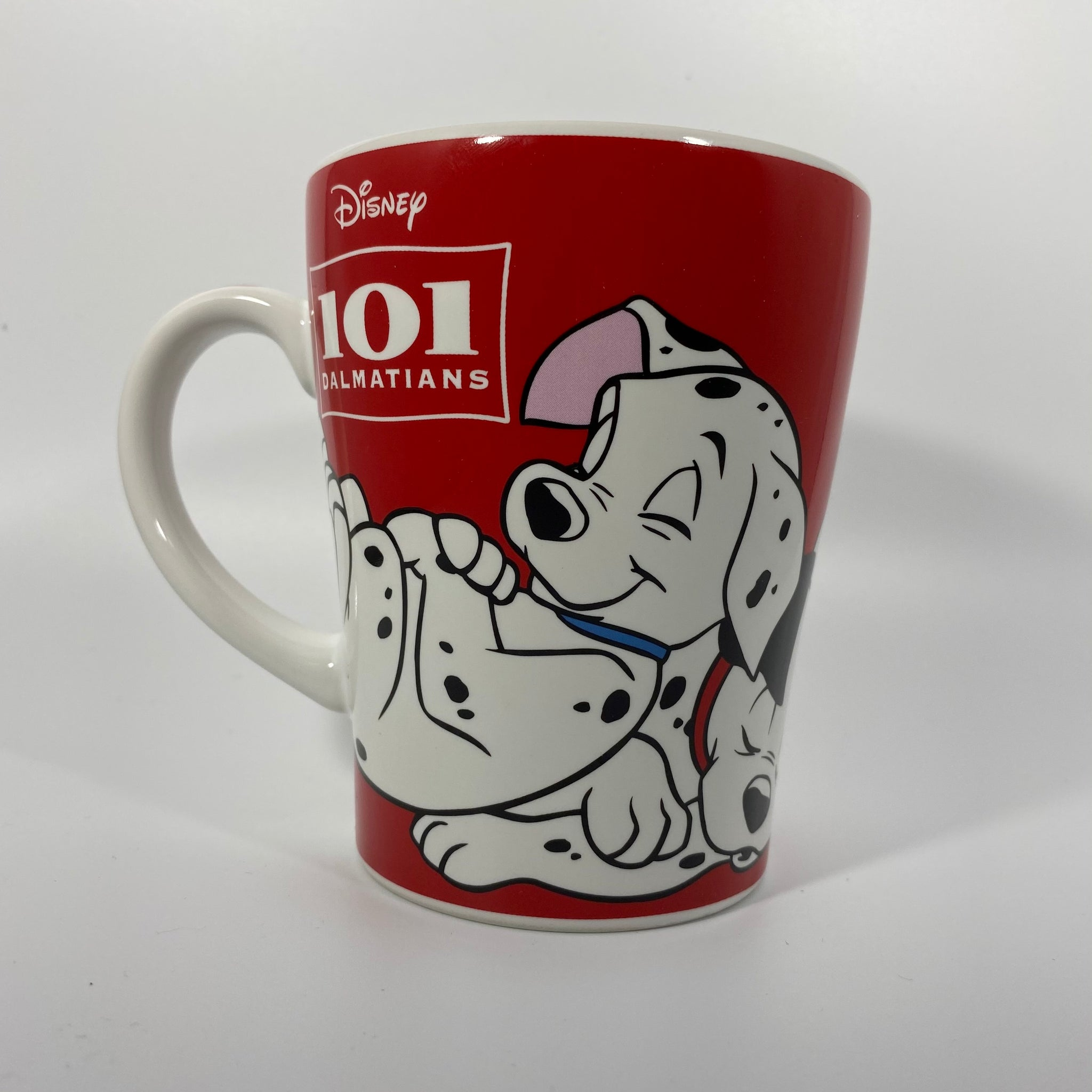 [Front View] Dark Red Base mug, with White Handle. Mug Has photo of multiple of the dalmation puppies from 101 dalmations on one another sleeping all around the mug; all the puppies are in full color. Next to the Image, there is the 101 dalmations logo in print with a square framed border around it,  and the disney logo on top, all in white.