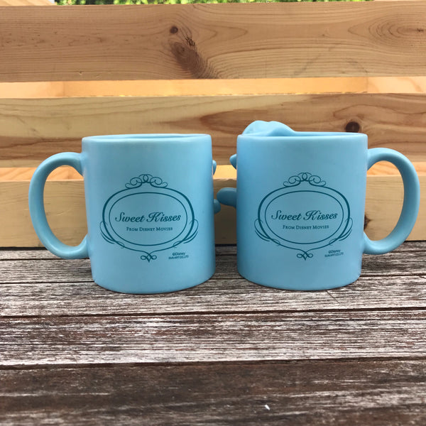 "[Back View] Both Mugs on the back say Sweet Kisses in script with a smaller writing of ""from disney movies"" right under in print, surrounded by a thin circular ornate frame outline. All is in dark blue."