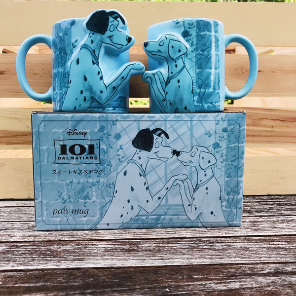 [Front View] Pair of pastel blue mugs, 1 Mug has male Dalmation, and the other, a female Dalmation facing eachother.  Both drawn in a black outline with watercolor background of flowers and a brick wall in darker shade of blue.